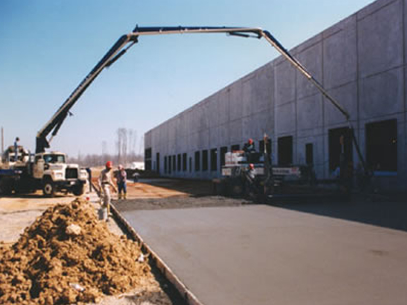 Security Capital Trust tilt-up warehouse construction project scene with workers pouring the flatwork concrete pavement sidewalks
